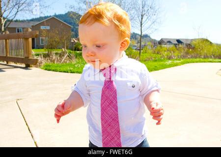 Ein kleiner Junge spielt im Park am Sonntag beste Kleidung einschließlich eine Krawatte um den Hals tragen. - Stockfoto