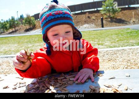 Ein ein-Jahr-alte Junge spielt in einem Park im Freien mit Hackschnitzel und Strukturen um ihn zu unterhalten. - Stockfoto