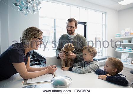 Tierarzt Gruß Familie mit Hund an der Rezeption - Stockfoto