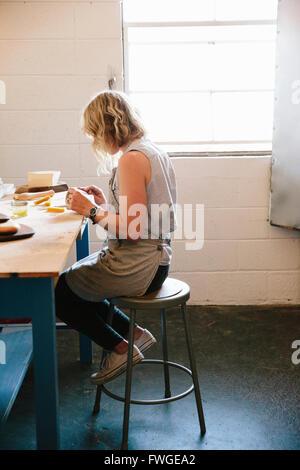 Eine Frau sitzt auf einem Stuhl in einem Workshop.