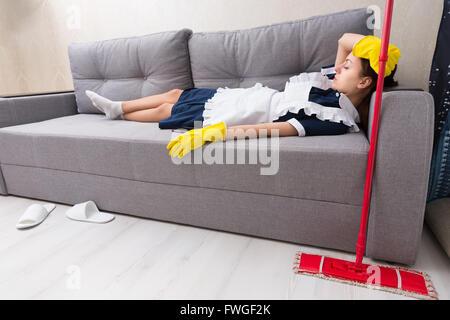 Entspannen Sie sich auf den Job auf einer Couch in ihrem einheitlichen ein Nickerchen mit ihren Mopp neben erschöpft - Stockfoto