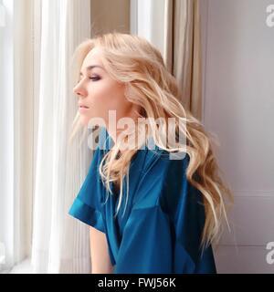 Seitenansicht der schönen Frau aus Fenster - Stockfoto