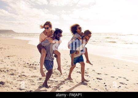 Zwei schöne junge Paare zu Fuß am Strand entlang, mit Männern geben Huckepack Fahrt für Frauen. Huckepack-Spiele auf Strandurlaub.
