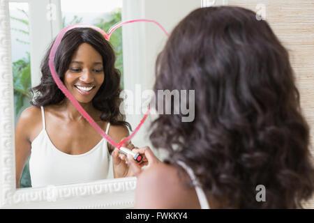 Schöne junge Frau zeichnen großes Herz auf Spiegel - Stockfoto
