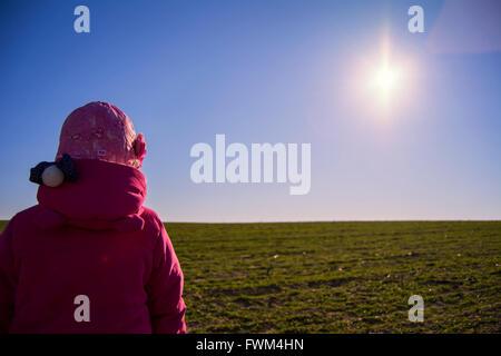 Rückansicht des Mädchen In rosa Jacke auf Wiese gegen Himmel - Stockfoto