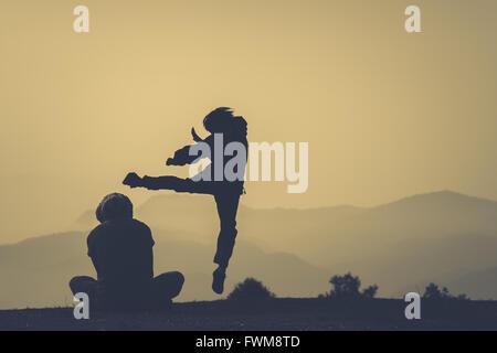zwei silhouette menschen springen mitten in der luft gegen den himmel bei sonnenuntergang. Black Bedroom Furniture Sets. Home Design Ideas