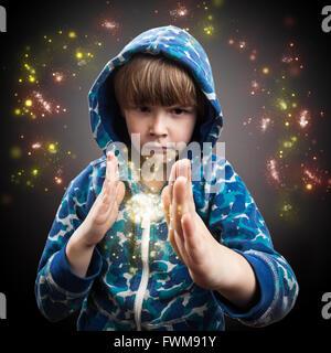 Porträt der junge Zauberer mit funkelt vor grauem Hintergrund - Stockfoto