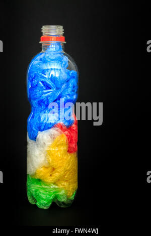 Kunststoff Flasche Wasser voller Plastiktüten auf schwarzem Hintergrund. Konzept-Bild für die Verschmutzung von - Stockfoto