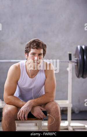Junger Mann mit Ohrhörer sitzen seine privaten Fitnessraum bereit für eine Sitzung - Stockfoto