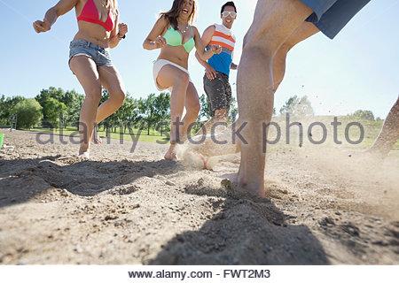 Gruppe von Freunden Fußball spielen am Strand - Stockfoto