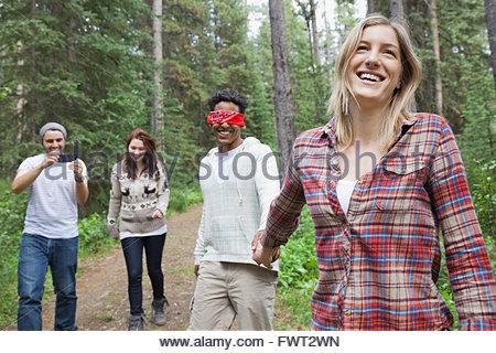 Frau mit verbundenen Augen Mann führt durch den Wald - Stockfoto