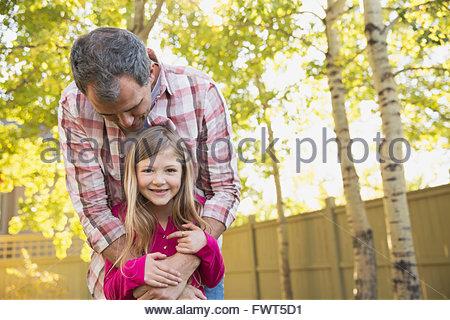 Porträt von glückliche Tochter mit Vater umarmt sie von hinten - Stockfoto