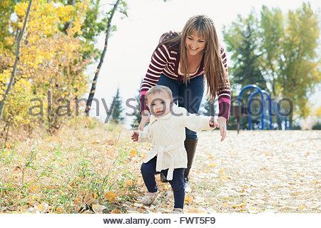 Mutter Babymädchen im Park laufen helfen - Stockfoto
