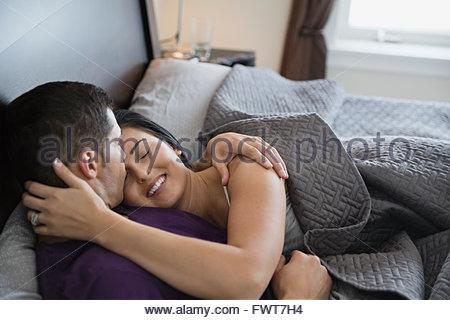 Romantisches Paar küssen und umarmen im Bett - Stockfoto