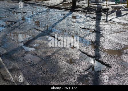 Mit Wasser gefüllte Schlaglöcher auf Asphaltstraße - Stockfoto