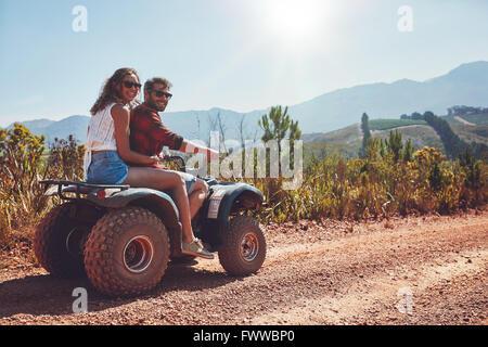 Porträt von Liebespaar in der Natur auf einer off-Road Fahrzeug. Junger Mann und Frau genießen ein Quad-Bike fahren - Stockfoto