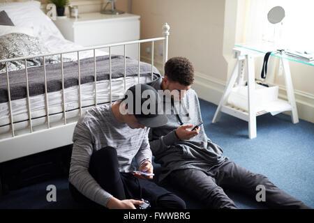 Zwei männliche Studenten im Schlafzimmer überprüfen Sie Nachrichten auf dem Handy