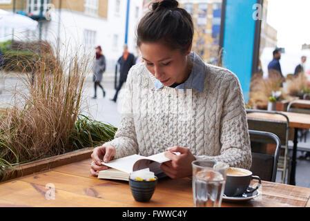 Junge Frau Lesebuch In Coffee-Shop - Stockfoto