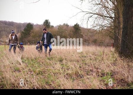 Familie Winter-Spaziergang durch Feld zusammen - Stockfoto