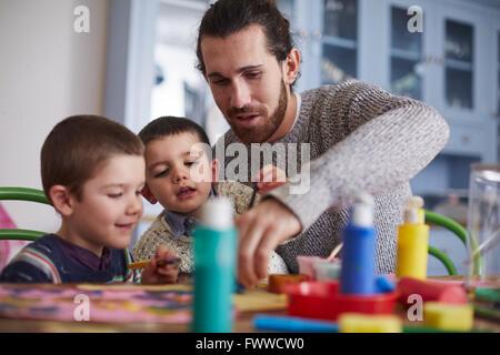 Vater und Söhne sitzen am Küchentisch und Paint-Bild - Stockfoto