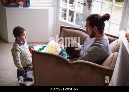Vater In Stuhl sitzen zu Hause lesen Geschichte Söhnen - Stockfoto