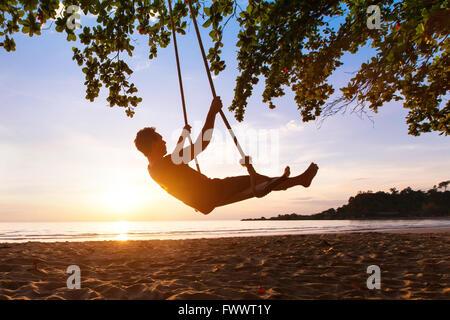 Swing auf Paradies tropischen Strand bei Sonnenuntergang, glückliche Menschen, die genießen Sommer Stockfoto