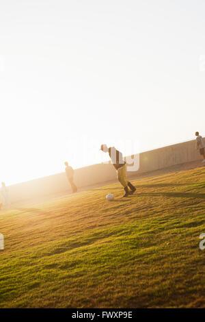 Südafrika, vier Männer (14-15, 16-17) Fußball spielen im park - Stockfoto