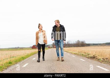 Schweden, Ostergotland, Mjolby, Teenage Mädchen (14-15) und junger Mann zu Fuß entlang der Landstraße - Stockfoto