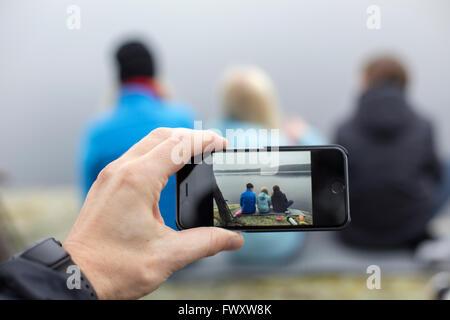 Schweden, Vastergotland, Lerum, Harskogen, Harsjon, Mann, Bild von Frau mit zwei Söhnen (10-11, 12-13) mit smartphone - Stockfoto