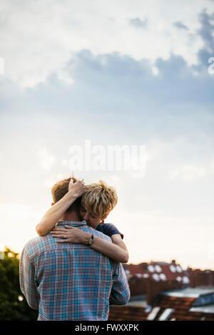 Deutschland, Berlin, junges Paar umarmt auf Dachterrasse bei Sonnenuntergang - Stockfoto