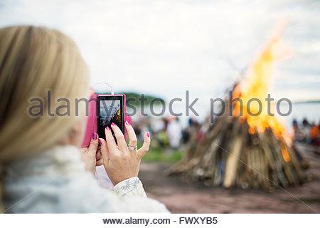 Finnland, Nyland, Helsinki, Drumso, Frau fotografieren Lagerfeuer mit ihrem smartphone - Stockfoto