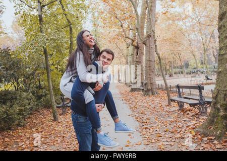 glückliche junge Paare, die Spaß im Herbst Park, Huckepack-kaukasische Familie, Mann und Frau, - Stockfoto