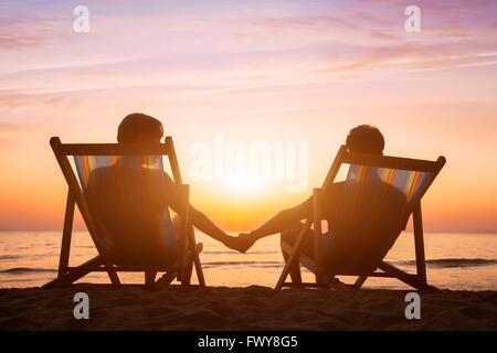 romantische Liebe Hintergrund, Flitterwochen, paar entspannend am Strand bei Sonnenuntergang Stockfoto