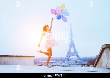 Traum-Reisen, Mädchen mit Luftballons springen in der Nähe von Eiffelturm in Paris - Stockfoto