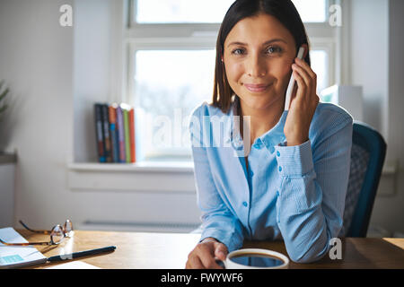 Lächelnd, glücklich junge Geschäftsfrau, arbeiten von Zuhause sitzt an ihrem Schreibtisch einen Anruf auf ihr Handy - Stockfoto