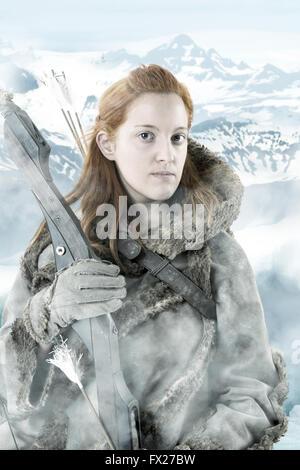 Wildes Mädchen Bogenschütze im Schnee mit Bogen - Stockfoto
