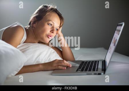 Hübsche, junge Frau mit ihrem Laptop-Computer im Bett (Farbe getönt Bild; flachen DOF) - Stockfoto