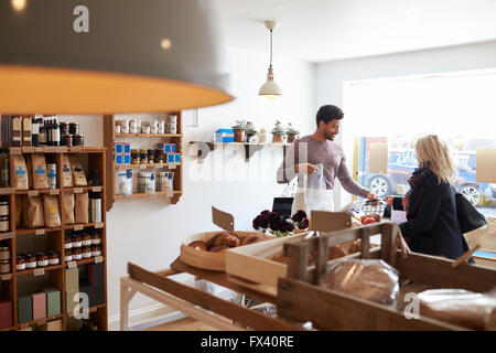 Männliche Verkäufer dienen Kundin In Feinkost - Stockfoto