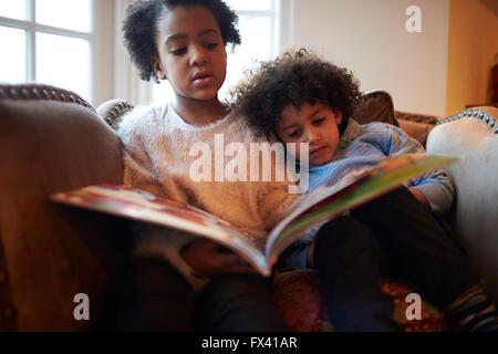 Bruder und Schwester Lesebuch auf Sofa zusammen - Stockfoto