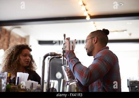 Dienst am Kunden im belebten Bar Barkeeper - Stockfoto