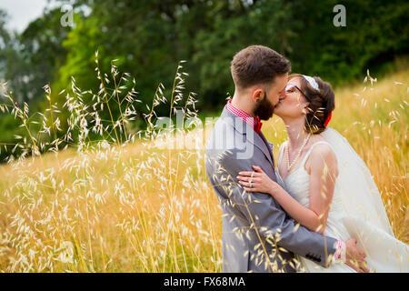 Braut und Bräutigam küssen in einem Feld am Tag ihrer Hochzeit. - Stockfoto