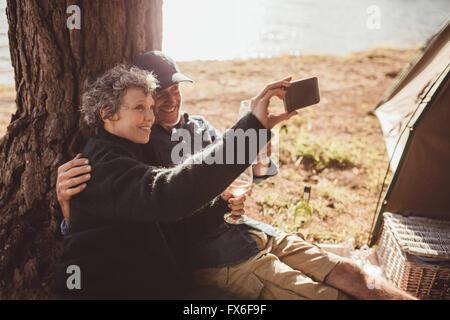 Aufnahme eines älteren Paares ein Foto von sich selbst, während draußen ein Zelt. Älteres paar camping am Ufer eines - Stockfoto