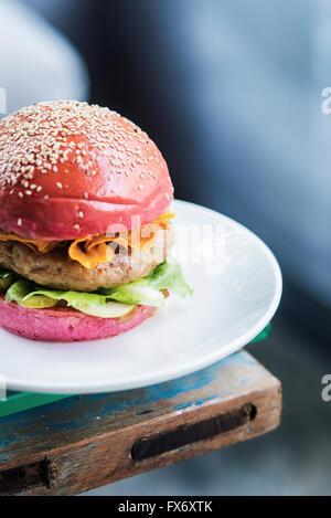 Chicken Burger mit Gurken und Chips in rote Beete Brot Brötchen - Stockfoto