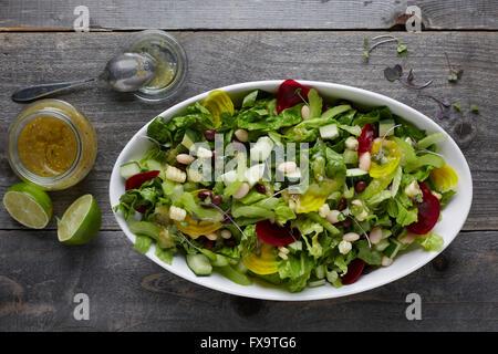 Weiße Keramik Schüssel voller frischer gemischter Blattsalat mit gesunden Belag, erschossen areal Ansicht mit Vinaigrette und Linden neben th