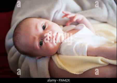 Ein Closeup Ernte Neugeborenen Baby Boy in die Kamera schaut, während er in den Armen seiner Mutter gehalten wird - Stockfoto