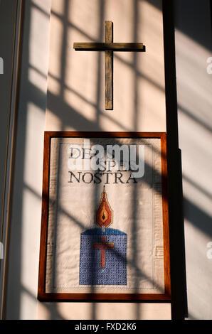 Licht durch ein Fenster auf ein lateinisches Wandteppich mit Inschrift und Holzkreuz. Deus Spes Nostra. Gott ist - Stockfoto