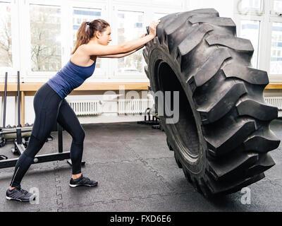 Foto von einer attraktiven jungen Frau mit einem Traktorreifen in einem Crossfit Gym trainieren. - Stockfoto