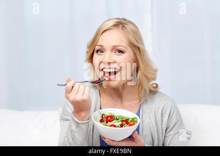 lächelnd Mitte im Alter Frau zu Hause essen Salat - Stockfoto