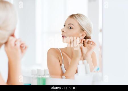 Frau versucht auf Ohrring Badezimmerspiegel betrachten - Stockfoto