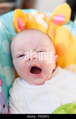 Ein Baby gähnt sitzend in seine Wippe nach seinen feed - Stockfoto